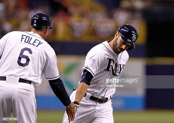 Sean Rodriguez of the Tampa Bay Rays celebrates with third base coach Tom Foley of the Tampa Bay Rays as he rounds the bases after hitting a threerun...