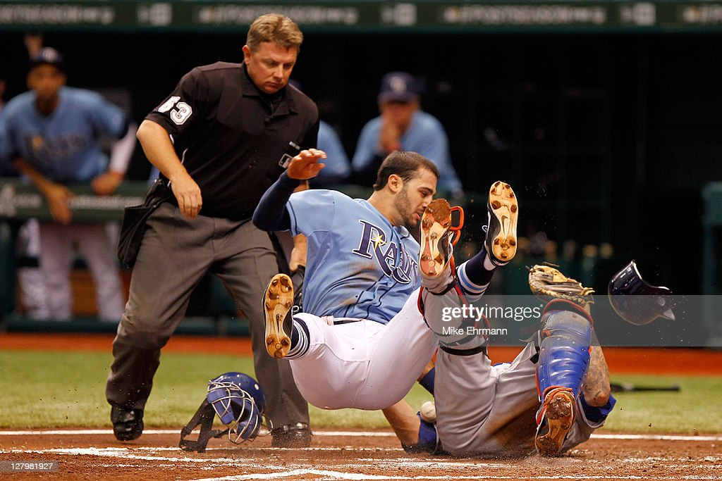 Sean Rodriguez of the Tampa Bay Rays crashes into Mike Napoli of the Texas Rangers to score on a play at the plate on a double by Matt Joyce in the...