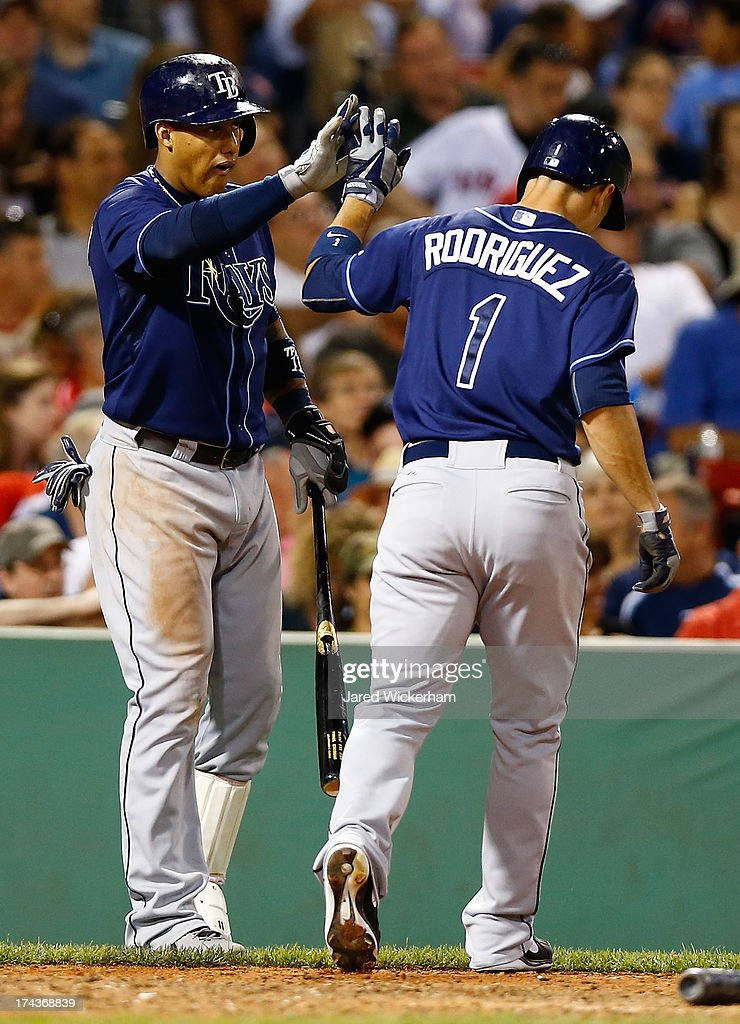 Sean Rodriguez #1 of the Tampa Bay Rays is congratulated by teammate Yunel Escobar #11 of the Tampa Bay Rays after scoring in the 8th inning against the Boston Red Sox during the game on July 24, 2013 at Fenway Park in Boston, Massachusetts.