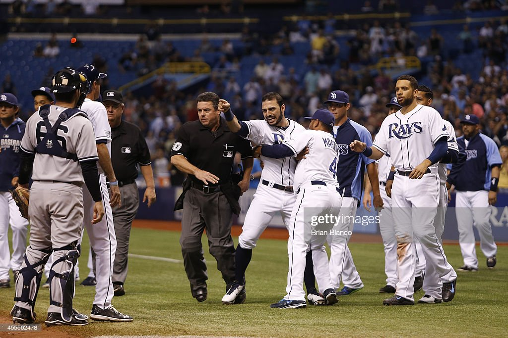 Sean Rodriguez of the Tampa Bay Rays is restrained by umpire Rob Drake and bench coach Dave Martinez after the New York Yankees' and the Tampa Bay...