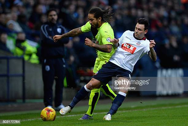 Sean Scannell of Huddersfield Town is tackled by Mark Davies of Bolton during the Sky Bet Championship match between Bolton Wanderers and...