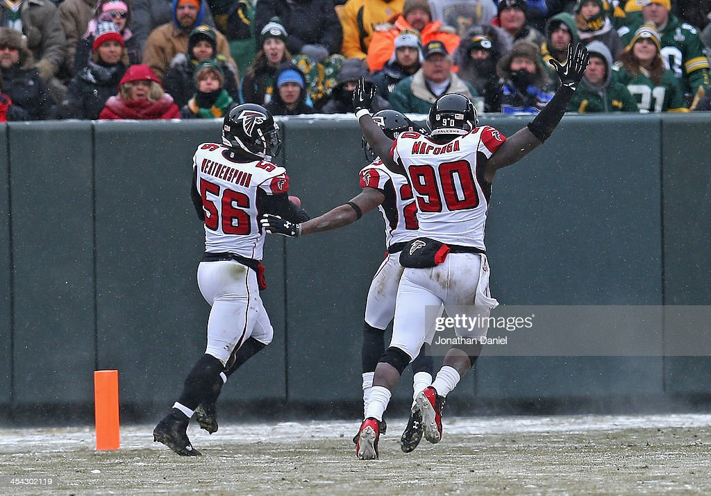 <a gi-track='captionPersonalityLinkClicked' href=/galleries/search?phrase=Sean+Weatherspoon&family=editorial&specificpeople=4532907 ng-click='$event.stopPropagation()'>Sean Weatherspoon</a> #56 of the Atlanta Falcons crosses the goalline with teammates including <a gi-track='captionPersonalityLinkClicked' href=/galleries/search?phrase=Stansly+Maponga&family=editorial&specificpeople=7363524 ng-click='$event.stopPropagation()'>Stansly Maponga</a> #90 after intercepting a pass for a touchdown against the Green Bay Packers at Lambeau Field on December 8, 2013 in Green Bay, Wisconsin.