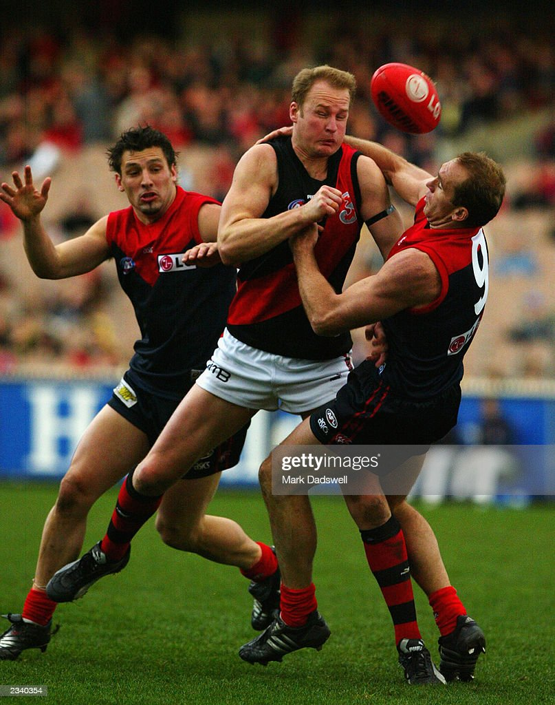 Sean Wellman of the Bombers comes under pressure from Russell Robertson and David Neitz of the Demons during the round 17 AFL match between the...