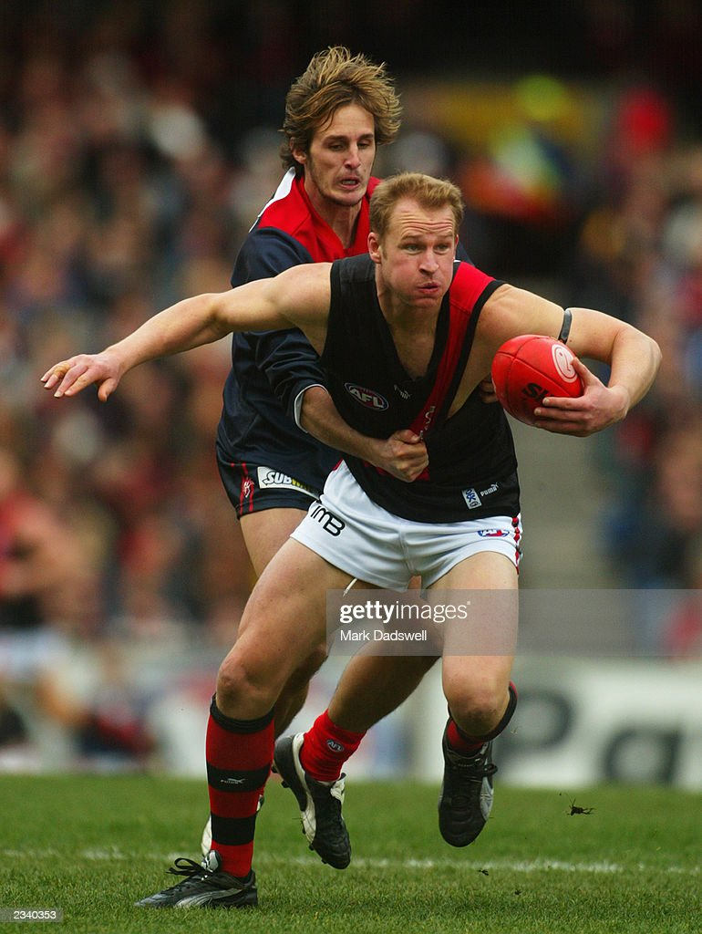 Sean Wellman of the Bombers is tackled by Travis Johnstone of the Demons during the round 17 AFL match between the Melbourne Demons and the Essendon...