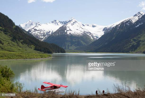Seaplane docked in still lake in mountain landscape, Anchorage, Alaska, Denali National Park, United States