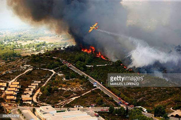 A seaplane drops water over a wildfire next to a residential area along the coastline near the Spanish resort of Javea Valencia region on September 5...
