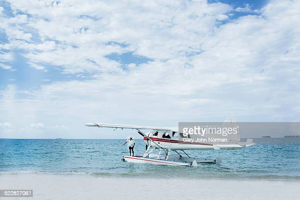 Seaplane landed on tropical beach.