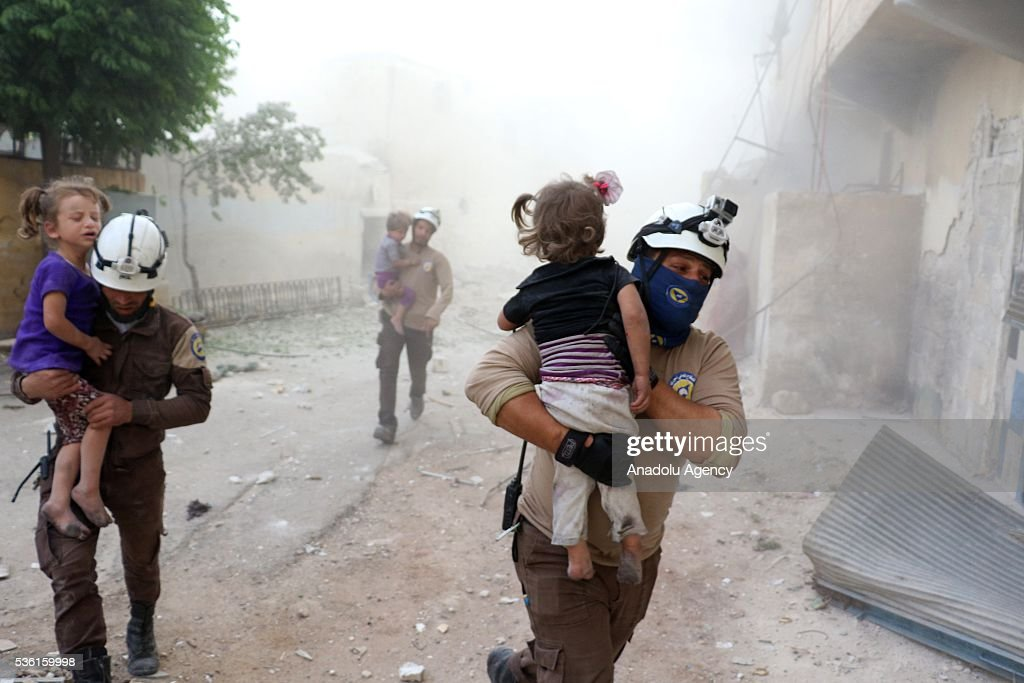 Searc and rescue team members carry wounded kids after Assad forces' airstrike, hit residential areas in Tal Zarazir Neighborhoof of Sukkeri District of Aleppo, Syria on May 31, 2016.