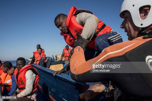 Search and rescue crew members from the Migrant Offshore Aid Station Phoenix vessel help rescue people from a small wooden boat on May 18 2017 off...