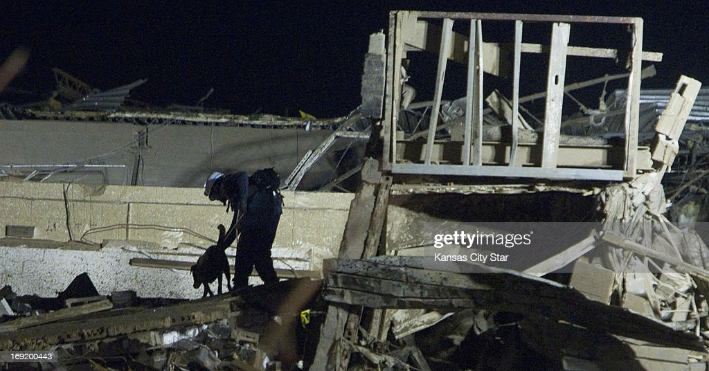 A search and rescue dog and its trainer work a pile of debris that was once Plaza Towers Elementary School after sounds were reported at the school. Emergency crews continued searching for children in the early morning hours on Tuesday, May 21, 2013, in Moore, Oklahoma, after a tornado ripped through part of the town. Emergency crews were hopeful that the sounds would lead to another rescue, but nobody appeared to be located.