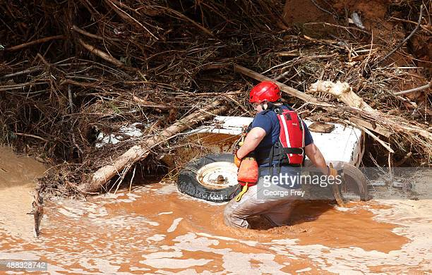 A search and rescue member searrches a buried vehicle in Short Creek where two vans were swept away the day before on September 15 2015 in Colorado...