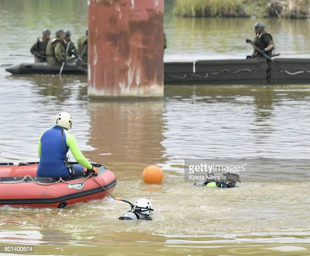 Search and rescue personnel continue efforts to look for missing people along the Chikugo River in Asakura Fukuoka Prefecture on July 24 2017 Six...