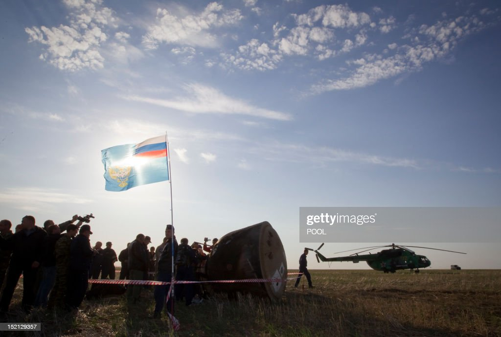 Search and rescue personnel work with the Soyuz TMA-04M capsule from the International Space Station (ISS) with crew of US astronaut Joseph Acaba and Russian cosmonauts Gennady Padalka and Sergei Revin after its landing near the town of Arkalyk in northern Kazakhstan, on September 17, 2012. A woman took today command of the ISS for only the second time as three US and Russian colleagues made a safe return from the orbiting space lab to the Kazakh steppe.