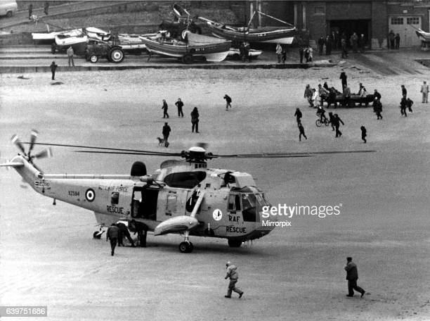 A RAF search and rescue Sea King from RAF Boulmer lands a man on the beach after he was plucked out of the sea off Cullercoats In the background is...