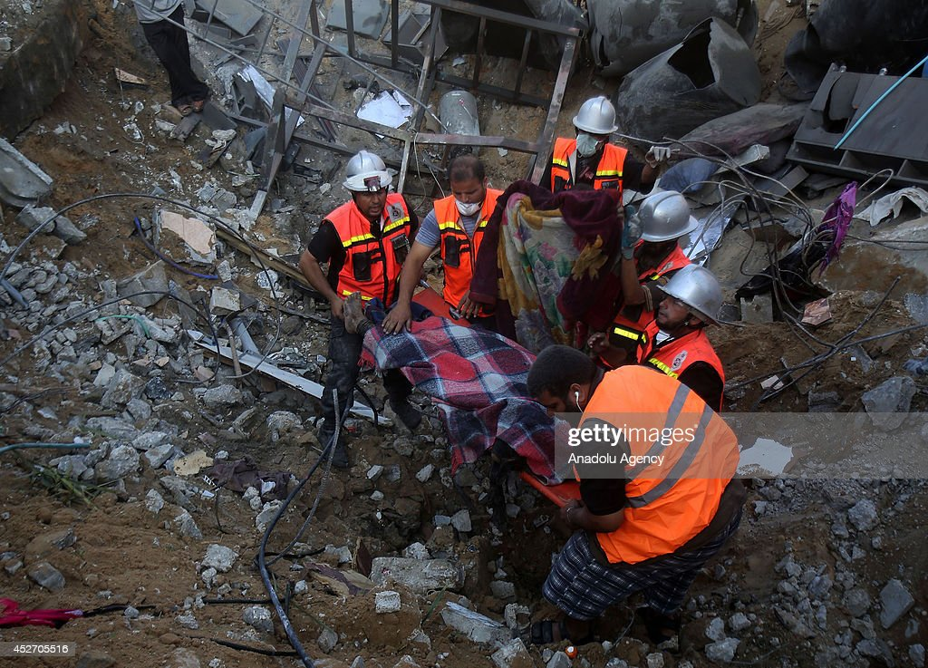 Search and rescue team and Palestinians search at the wreckage of a building, belongs to Palestinian En-Neccar family, in Khan Yunis, Gaza on July 26, 2014. Israeli assault, hit house of Palestinian En-Neccar family in Khan Yunis, killed 16 members of family and wounded 20 others in Gaza. The new fatalities raise Gaza's death toll from Israel's war to 900 since the beginning of this war on July 7.