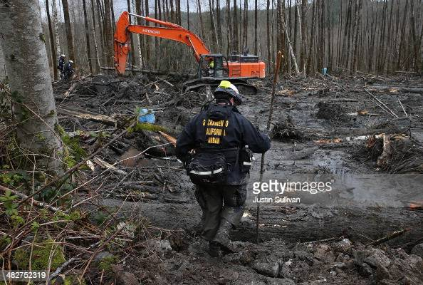 A search and rescue team from Sacramento California sifts through debris from a deadly mudslide on April 4 2014 in Oso Washington Workers continue to...