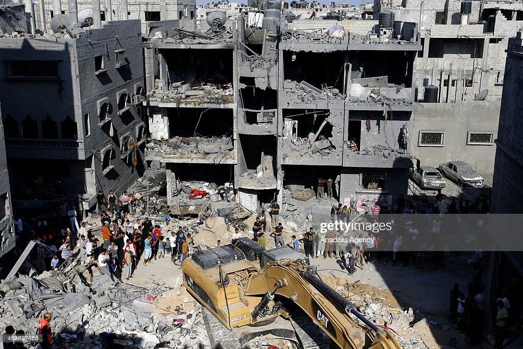 Search and rescue team members accompanied Palestinian local residents inspect the rubble of a destroyed house, after it was hit by an Israeli airstrike in Tel es-Sultan neighborhood of Rafah on August 21, 2014. Three senior military commanders of Izzedine al-Qassam Brigades, identified by Hamas as Mohammed Abu Shamaleh, Raed Attar and Mohammed Barhoum were killed by Israeli airstrikes in Tel es-Sultan neighborhood of Rafah.