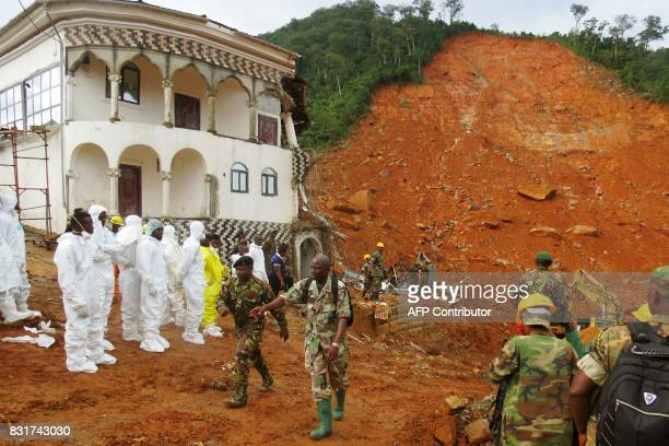 TOPSHOT Search and rescue team members and soldiers operate near a mudslide site and damaged building near Freetown on August 15 after landslides...
