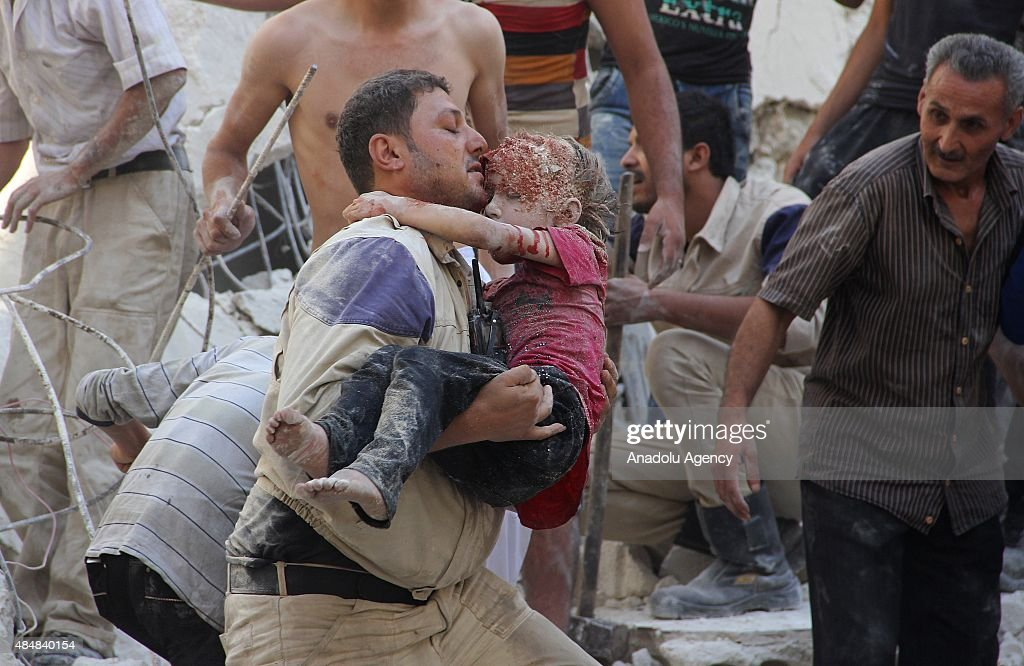 Search and rescue team members carry a girl after she was pulled out from debris following Assad forces barrel bomb attack to Qadi Askar neighborhood...