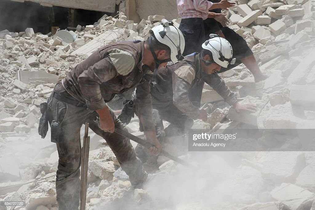 Search and rescue team members inspect the debris after Asad Regime's air-strike over residential areas at al-Maysir neighborhood of Aleppo, Syria on May 27, 2016.