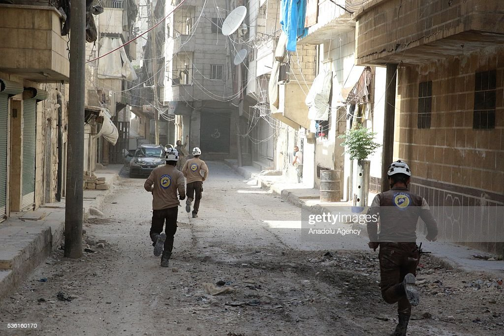 Search and rescue team members run to the attack site after Assad forces' airstrike, hit residential areas in Tal Zarazir Neighborhoof of Sukkeri District of Aleppo, Syria on May 31, 2016.