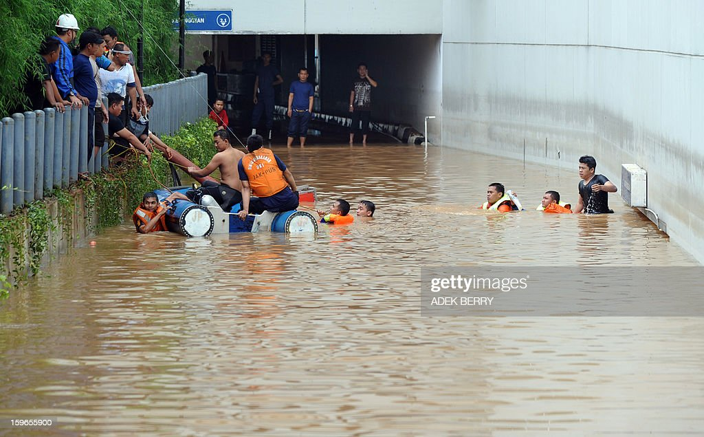 Search and rescue team members try to help people who were trapped in the basement of the UOB building after seasonal floods inundated much of downtown Jakarta on January 18, 2013. Floods in Indonesia's capital Jakarta have left at least 11 people dead and two missing, authorities said as murky brown waters submerged parts of the city's business district, causing chaos for a second day. AFP PHOTO / ADEK BERRY