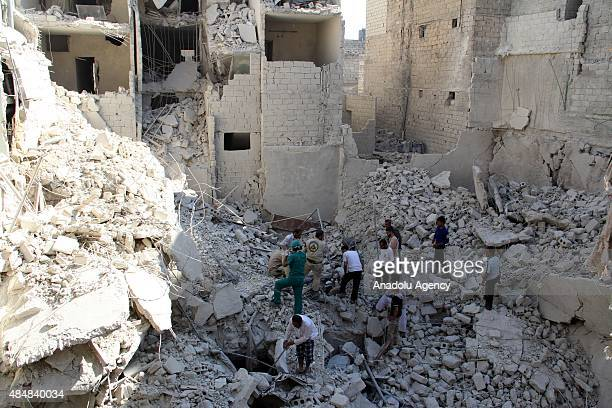 Search and rescue team members try to pull out Syrians from debris after Assad forces barrel bomb attack to Qadi Askar neighborhood leaving...