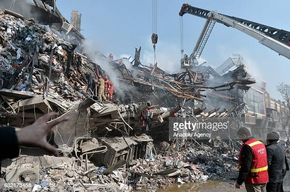 Search and rescue teams are seen on duty after the 15floor Plasco Tower one of central Tehrans bestknown commercial buildings collapsed after being...