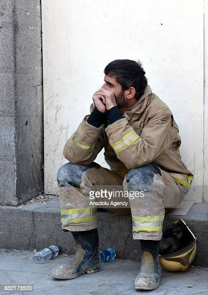 A search and rescue worker rests after the 15floor Plasco Tower one of central Tehrans bestknown commercial buildings collapsed after being gutted by...