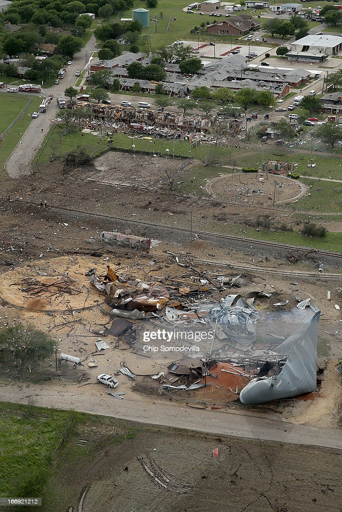 Search and rescue workers comb through what remains of a 50-unit apartment building (background) the day after an explosion at the West Fertilizer Company (foreground) destroyed the building April 18, 2013 in West, Texas. According to West Mayor Tommy Muska, around 35 people, including 10 first responders, were killed and more than 150 people were injured when the fertilizer company caught fire and exploded, leaving damaged buildings for blocks in every direction.