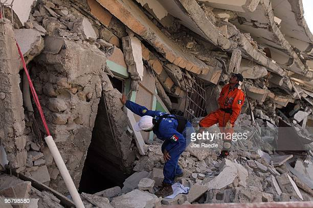 Search and Rescue workers from Mexico search for a way to reach survivors trapped under the rubble of what is left of the St Gerard building after...