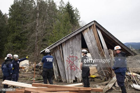 Search and rescue workers including firefighters from the Marysville Fire District inspect a damaged structure in the aftermath of a mudslide on...