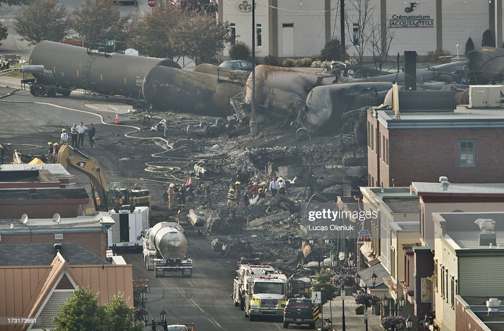 Search teams carry a large white bag out of the rubble in the town centre of Lac-MÈgantic during their search for the dead Monday evening. 40 more are missing after a train derailment caused a massive explosion early Saturday morning.