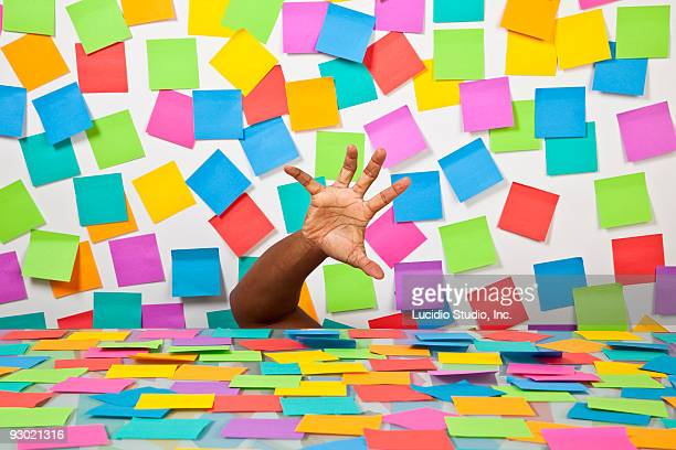 Searching hand amoung many Postit notes
