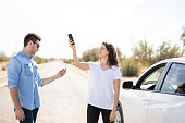 Young man and woman searching for reception signal on their smartphone with broken car on the road