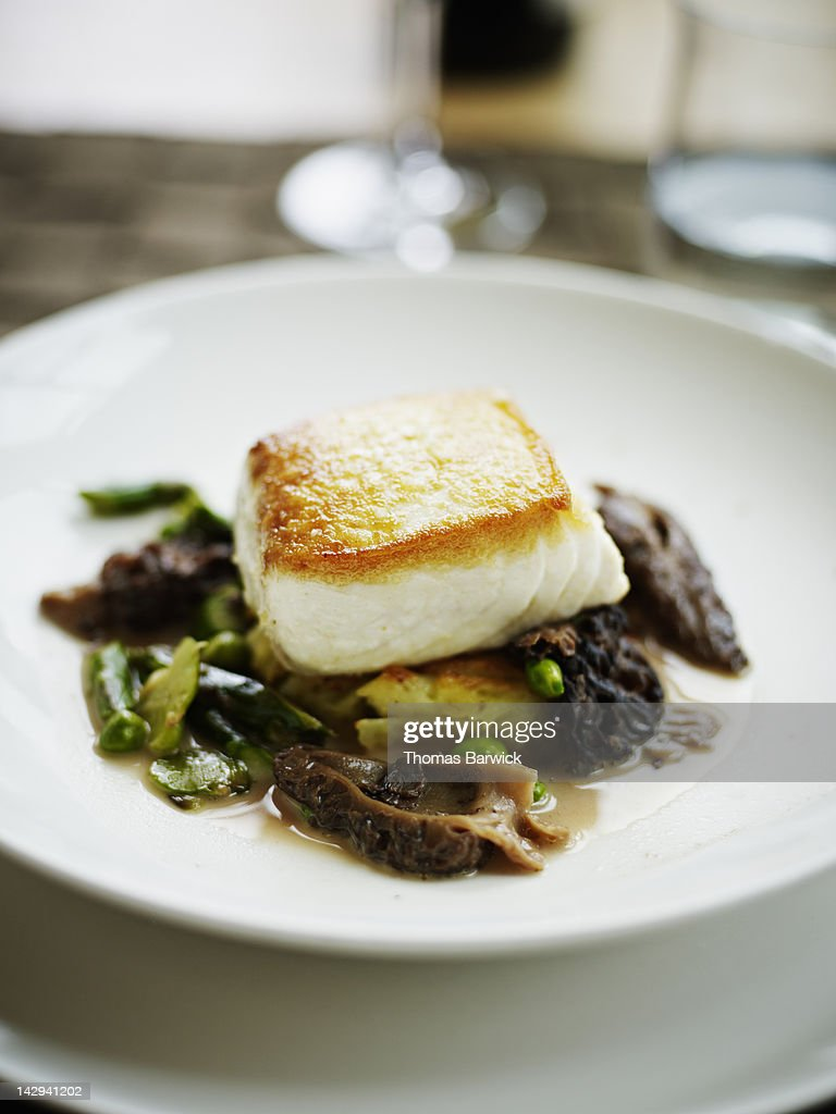 Seared halibut fillet with asparagus and morels : Stock Photo