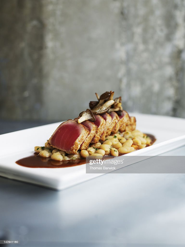 Seared spiced tuna with cannellini beans : Stock Photo