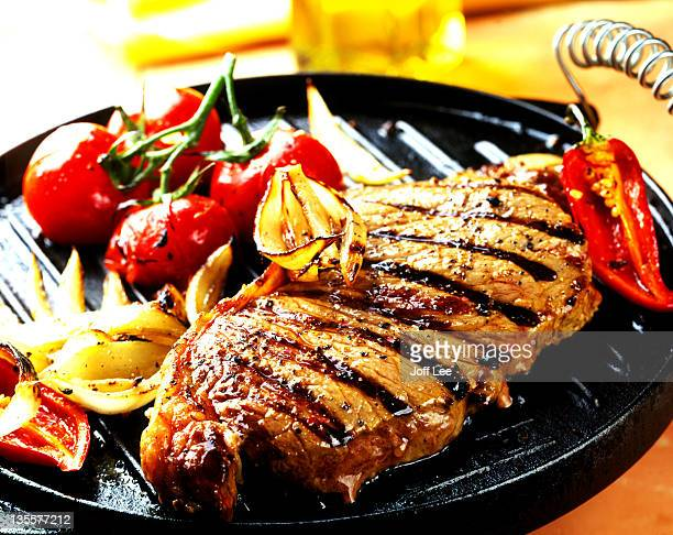 Seared steak on griddle pan with vegetables