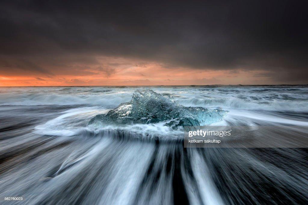 Seascape of lonely iceberg at Jokulsarlon beach
