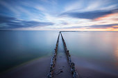 Seascape along the coast of the IJsselmeer in the Netherlands. The water looks smooth and the clouds are blurred because of a long exposure. The breakwaters lead to the horizon into infinity.