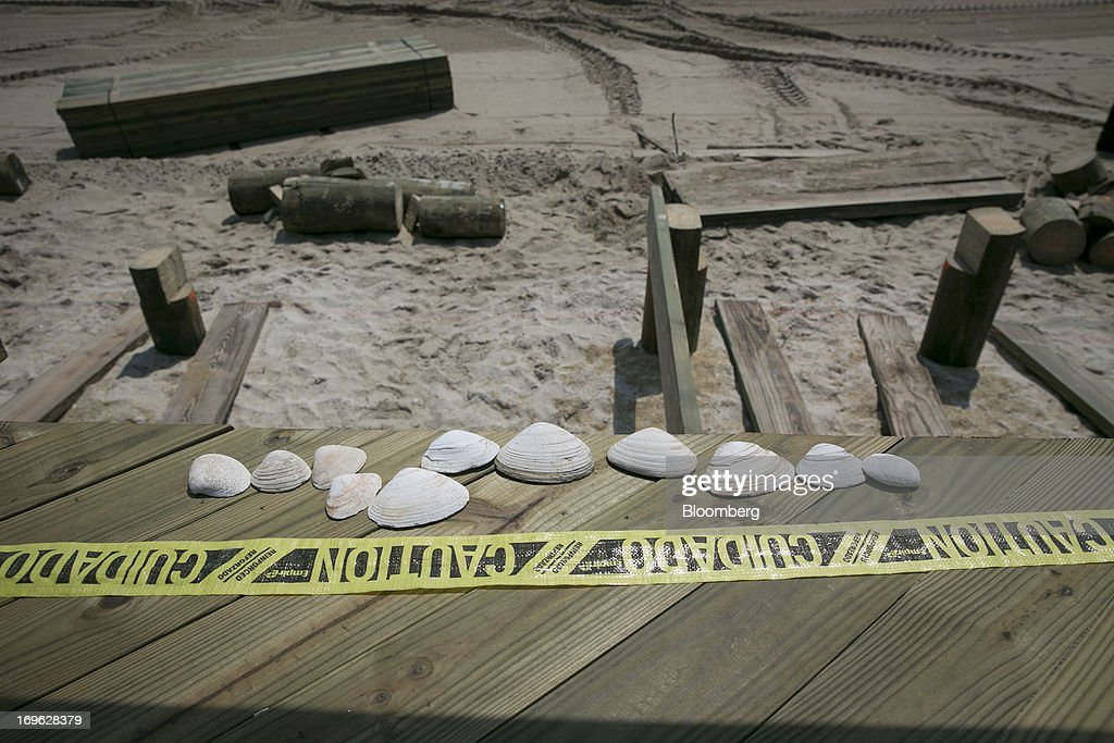 Seashells sit placed along a piece of yellow 'Caution' tape in Seaside Heights, New Jersey, U.S., on Wednesday, May 29, 2013. Sandy, which came ashore near Atlantic City, killed dozens of people and destroyed more than 365,000 homes in the state. Christie has said it will cost $36.9 billion for repairs and to prevent devastation from future storms. Photographer: Scott Eells/Bloomberg via Getty Images