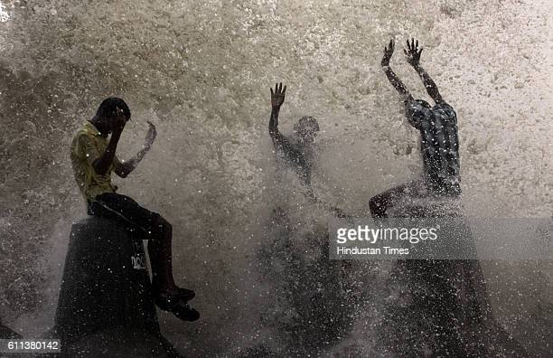Seashore Youth A group of boys perched on concrete tetrapods along the sea soaks up the showers as a huge wall of a sea wave lashes the parapet...