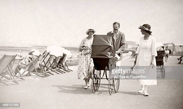 A seaside holiday postcard featuring a dapper gentleman pushing a pram accompanied by two ladies carrying tennis racquets circa 1920