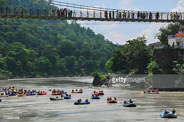 Season for rafting under the Laxman Jhula Bridge Rishikesh Uttarakhand India