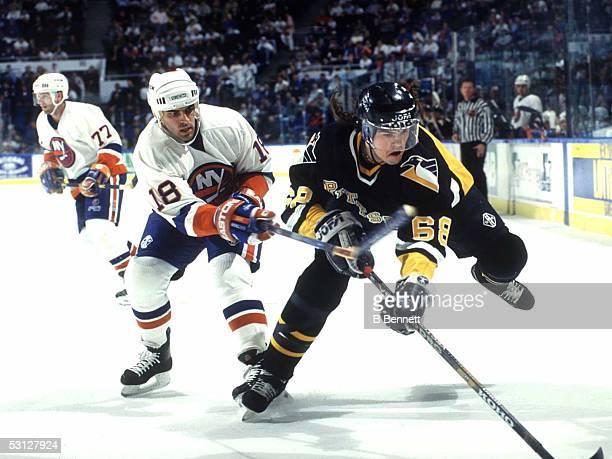 Islanders Marty McInnis trips up Pittsburgh's Jaromir Jagr