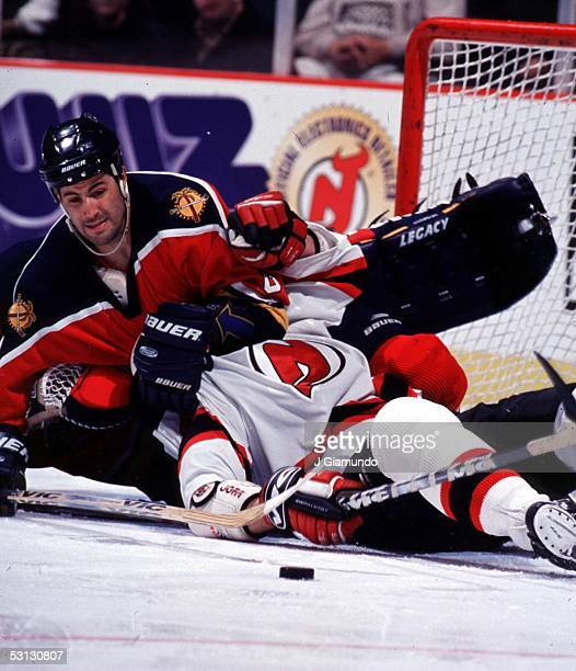 Jeff Norton of the Panthers puts a head lock on one of the Devils in a wild scramble for the loose puck