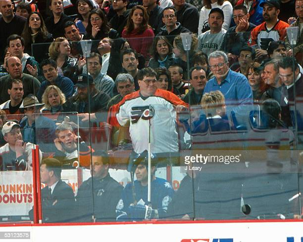Tie Domi of the Maple Leafs is accompanied by security after fighting with a fan that jumped the glass at the First Union Center