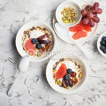 Petit-déjeuner sain saisonnier   yaourt, muesli chocolat, pamplemousse  rose, raisins, pistaches. Vue de dessus. Copiez l espace. lay plat 130f1d67549e