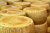 close up of a heap of  wheels of seasoned parmesan