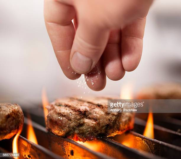 Seasoning hamburgers cooking on a barbeque
